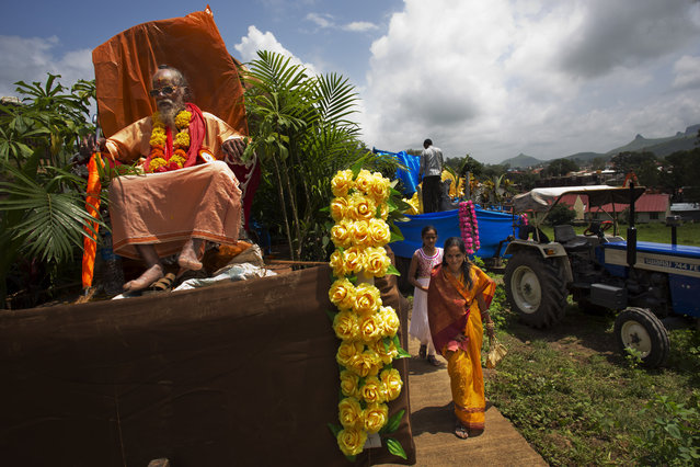 A Hindu Guru sits atop of a chariot as he participates in a procession during Kumbh Mela, or Pitcher Festival, at Trimbakeshwar, India, Thursday, August 27, 2015. Hindus believe taking a dip in the waters of a holy river during the festival will cleanse them of their sins. The festival is held four times every 12 years. (Photo by Bernat Armangue/AP Photo)