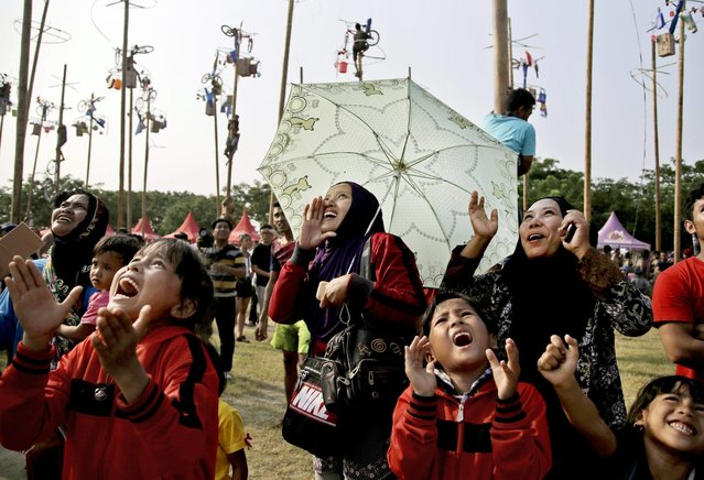 Indonesian women and children shout supports for family members who participate in a greased-pole climbing competition held as a part of the independence day celebrations in Jakarta, Indonesia, Sunday, August 17, 2014. (Photo by Dita Alangkara/AP Photo)