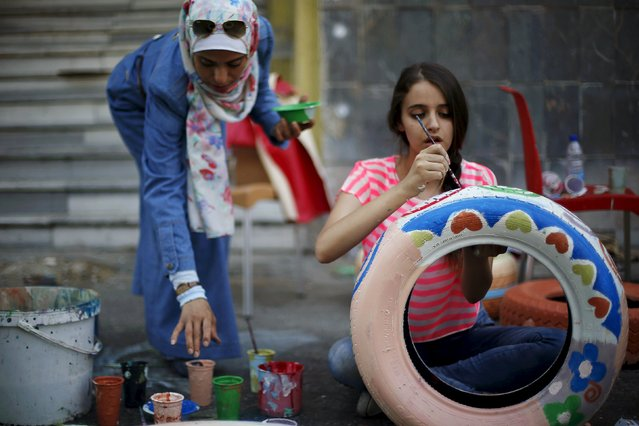"Volunteers paint and decorate tyres during an initiative titled ""Hajar-Waraka-Balad"" in Amman, Jordan, August 28, 2015. A number of Jordanian volunteers took part in the event organised by Sakeyat Addaraweesh, aiming to paint tyres that will be distributed as seats to decorate Amman's streets. (Photo by Muhammad Hamed/Reuters)"