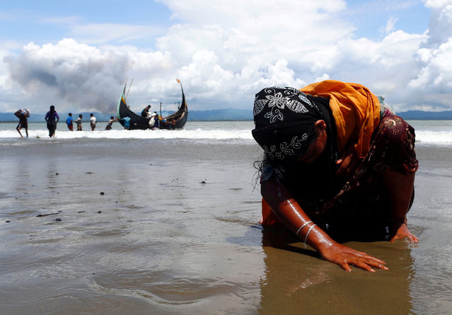 An exhausted Rohingya refugee woman touches the shore after crossing the Bangladesh-Myanmar border by boat through the Bay of Bengal, in Shah Porir Dwip, Bangladesh September 11, 2017. (Photo by Danish Siddiqui/Reuters)