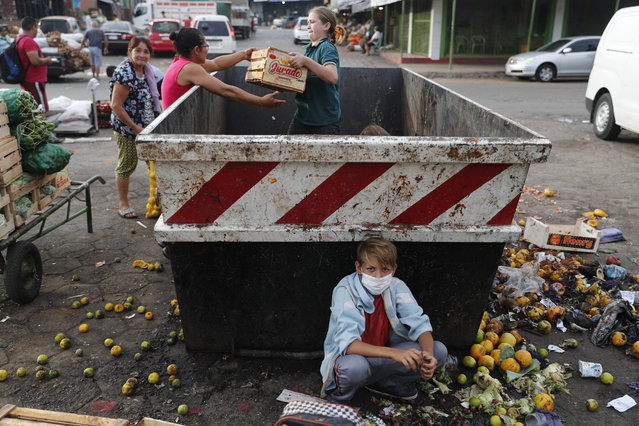 """Fabian Ramirez, 11, scavenges a trash container for vegetables with his family that were discarded at the """"Mercado de Abasto"""", a market for vendors, during the fourth week of a quarantine to help contain the spread of the new coronavirus in Asuncion, Paraguay, Thursday, April 2, 2020. COVID-19 causes mild or moderate symptoms for most people, but for some, especially older adults and people with existing health problems, it can cause more severe illness or death. (Photo by Jorge Saenz/AP Photo)"""