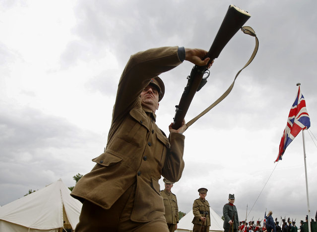 Custom silicone technician Corin Watts, portraying a Lance Corporal in the Kings Royal Rifle Corps, part of the Rifles Living History Society, participates in a rifle drill whilst recreating life as a First World War soldier at the Colchester Military Tournament in Colchester, eastern England July 6, 2014. (Photo by Luke MacGregor/Reuters)