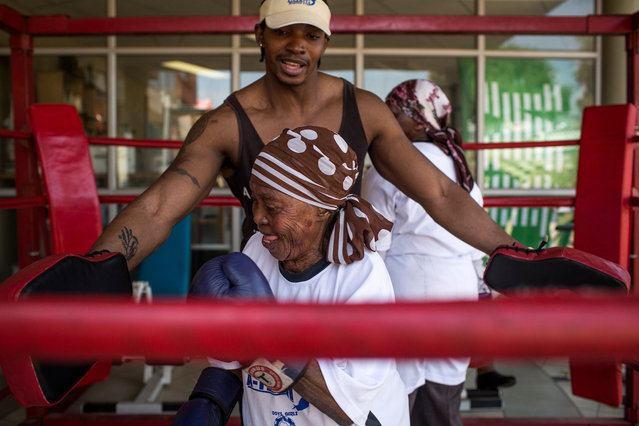 "74 year-old Zodwa Thwala (Front) spars with trainer Nqobile Khumalo as she takes part in a ""Boxing Gogos"" (Grannies) training session hosted by the A Team Gym in Cosmo City in Johannesburg on September 19, 2017. (Photo by Gulshan Khan/AFP Photo)"