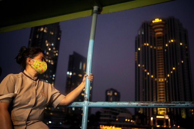 A woman wearing a face mask rides a boat as the Peninsula hotel lights up in tribute to the healthcare workers and people staying home to curb the spread of the coronavirus disease (COVID-19) outbreak in Bangkok, Thailand, April 14, 2020. (Photo by Athit Perawongmetha/Reuters)
