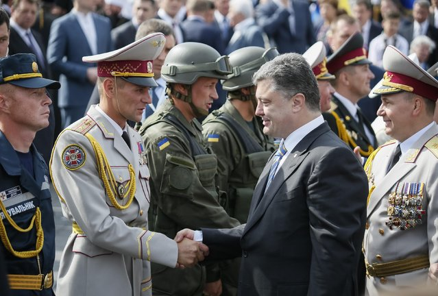 Ukraine's President Petro Poroshenko (2nd R) greets servicemen who participated in Ukraine's Independence Day military parade in the centre of Kiev August 24, 2014. Armored vehicles and soldiers, some of them hardened in battle, paraded on Kiev's main square on Sunday to mark Independence Day in a defiant show of the military force Ukraine's government hopes will defeat pro-Russian separatists in the east. (Photo by Gleb Garanich/Reuters)