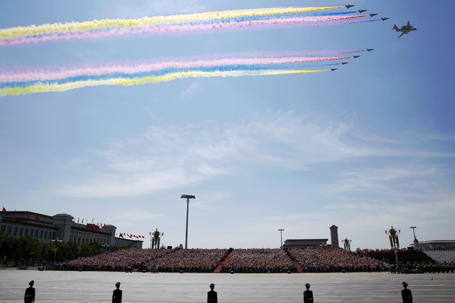 People watch while paramilitary policemen stand guard as military aircraft fly over the Tiananmen Square during the military parade marking the 70th anniversary of the end of World War Two, in Beijing, China, September 3, 2015. (Photo by Damir Sagolj/Reuters)