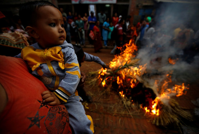A woman carries a child as an effigy of the demon Ghantakarna burns, to symbolize the destruction of evil, during the Ghantakarna festival at the ancient city of Bhaktapur, Nepal August 1, 2016. (Photo by Navesh Chitrakar/Reuters)
