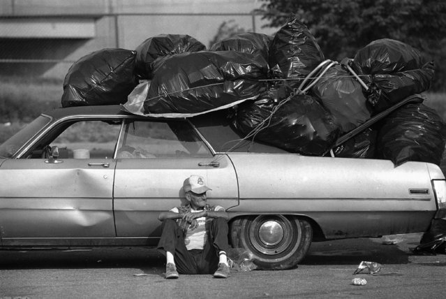 His car heeped with bags filled with aluminum cans, Charles Miller of Philadelphia takes a break from collecting the cans in the parking lots outside Philadelphia's JFK Stadium Sunday morning, July 14, 1985. Parking lots surrounding the stadium were scattered with bottles and cans and garbage following Saturday's Live Aid concert. (Photo by Amy Sancetta/AP Photo)