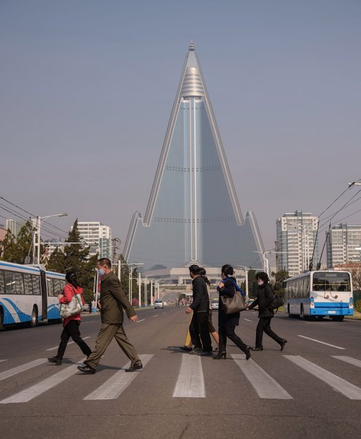 "People wearing face masks walk across a street before the Ryugyong hotel (back C) on the occasion of the 108th birthday of late North Korean leader Kim Il Sung, known as the ""Day of the Sun"", in Pyongyang on April 15, 2020. (Photo by Kim Won Jin/AFP Photo)"
