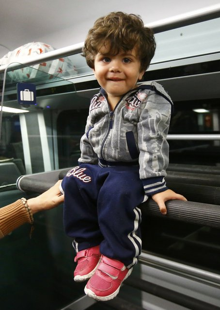A migrant boy sits aboard a train to Vienna departed from the railway station in the town of Hegyeshalom, Hungary, September 5, 2015. (Photo by Leonhard Foeger/Reuters)