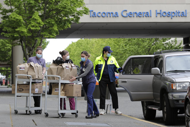 "J.D. Elquist, right, of the Downtown Tacoma Partnership, delivers meals to workers at Tacoma General Hospital in Tacoma, Wash., Wednesday, April 29, 2020. The delivery was part of the organization's ""Hero Meals"" project, which collects donations from the public to purchase meals from restaurants that are then given to healthcare workers, first responders, and other essential workers in the city during the coronavirus outbreak. (Photo by Ted S. Warren/AP Photo)"