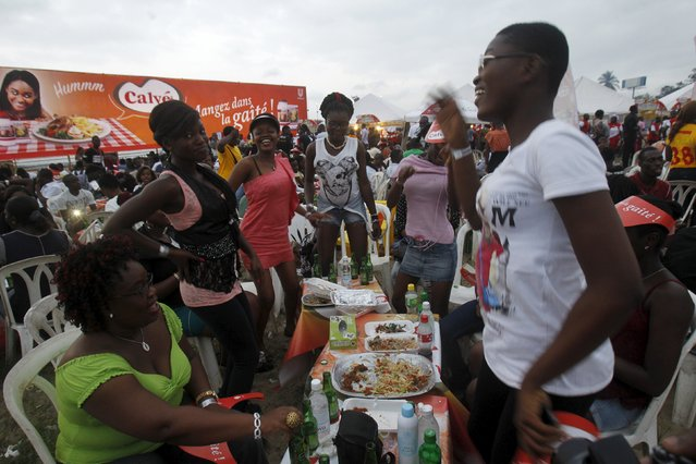 Girls dance at their dining table during the Festival des Grillades, in the yard of the Culture Palace of Abidjan, September 5, 2015. (Photo by Luc Gnago/Reuters)