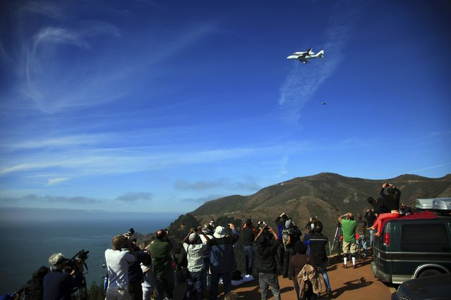 Onlookers at the Golden Gate National Recreation Area, near the Golden Gate Bridge in San Francisco, watch Endeavour pass overhead. (Photo by Jim Wilson/The New York Times)