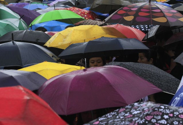 """Participants for """"Walk for Peace"""" use umbrellas in the rain brought on by Typhoon Kalmaegi, also called Luis, at Luneta park in Manila September 14, 2014. Tropical Storm Kalmaegi intensified into a typhoon on Saturday, and continues to build moving farther towards the northern provinces, the state weather bureau reported. (Photo by Romeo Ranoco/Reuters)"""