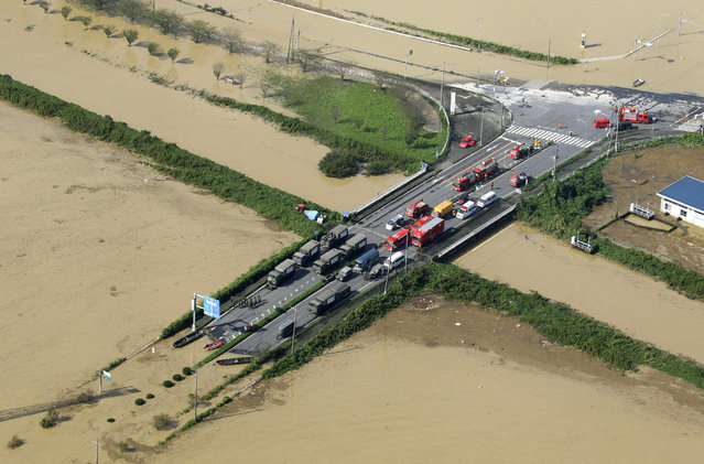 Vehicles of the Ground Self-Defense Force and firefighters are parked at a partially submerged road during a rescue operation in Joso, Ibaraki prefecture, northeast of Tokyo, Friday, September 11, 2015. Rescue workers searched through the flooded city on Friday, hunting for missing people a day after raging floodwaters broke through an embankment and washed away houses and forced dozens of people to rooftops. (Photo by Masanori Takei/Kyodo News via AP Photo)