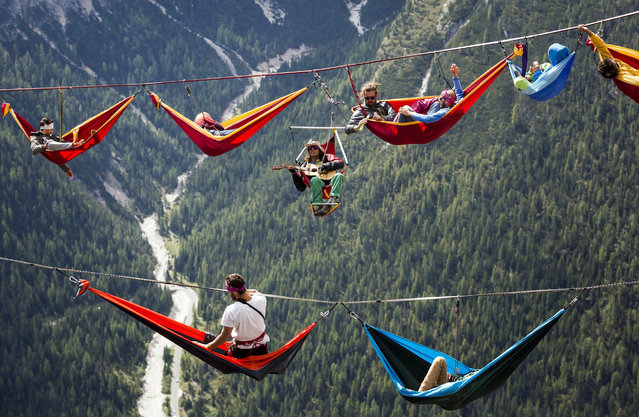 A picture made available on 17 September 2014 shows extreme athletes resting in hammocks on webbings stretched between rocks during the International Highline Meeting in Monte Piana, near Misurina, in the northern Italian Alps, Italy, 08 September 2014. (Photo by Balazs Mohai/EPA)