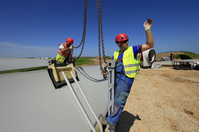 Employees work on a rotor blade of a turbine in Meneslies, France July 17, 2014. (Photo by Benoit Tessier/Reuters)