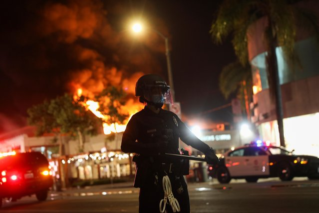 A law enforcement officer takes position as a building burns during nationwide unrest following the death in Minneapolis police custody of George Floyd, in Los Angeles, California, U.S., May 30, 2020. (Photo by Patrick T. Fallon/Reuters)