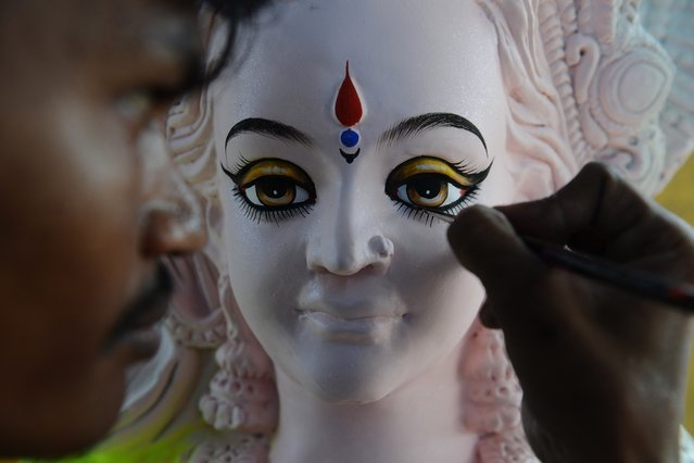 An Indian artist gives final touches to a statue of the Hindu goddess Durga ahead of the forthcoming Dushhera-Vijaya Dashami festival at a workshop in Hyderabad on September 22, 2014. Durga Puja, the annual Hindu festival that involves worship of the goddess Durga who symbolizes power and the triumph of good over evil in hindu mythology, culminates in the immersion of idols in water bodies. (Photo by Noah Seelam/AFP Photo)