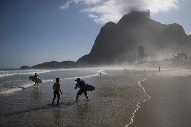"""Ricardo Ramos, third from left, founder of Rocinha Surf School, gives a surfing class to children on Sao Conrado beach in Rio de Janeiro, Brazil, Saturday, August 13, 2016. """"The kids often get mycosis, white spots on their skins"""", Ramos said about his students who surf without a bodysuit and just wear board shorts. """"But there's nothing we can do about it and they've built antivirus. Favela surf has no luxuries"""". (Photo by Felipe Dana/AP Photo)"""