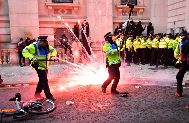 A firework explodes as police officers clash with demonstrators in Whitehall during a Black Lives Matter protest in London, following the death of George Floyd who died in police custody in Minneapolis, London, Britain, June 7, 2020. (Photo by Dylan Martinez/Reuters)