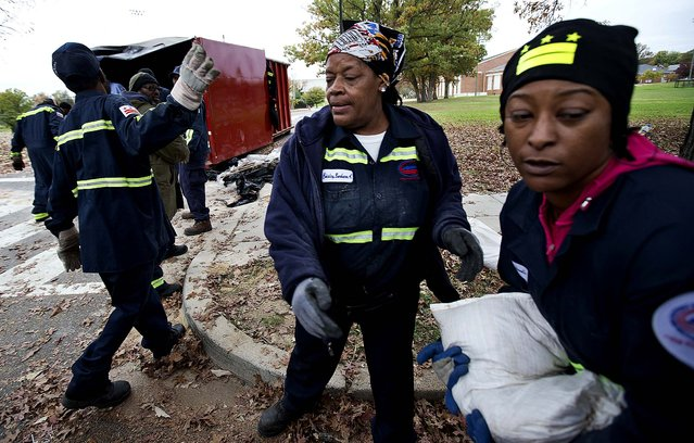 District of Columbia Department of Public Works workers pass out free sandbags to DC residents in Washington on Sunday. (Photo by Manuel Balce Ceneta/Associated Press)
