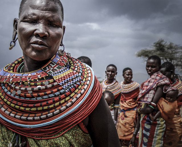 """Maasai Women"". A Maasai women stands before her tribe. Photo location: Maasai Mara, Kenya. (Photo and caption by Seth Langbauer/National Geographic Photo Contest)"