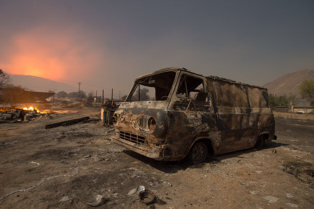 Seen in a long exposure nighttime photograph, a burned van rests in a lot while a wildfire glows on the horizon in Phelan, Calif., early Thursday, August 18, 2016 2016. (Photo by Noah Berger/AP Photo)