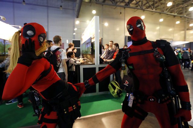 "Participants dressed in costumes of Marvel Comics character ""Deadpool"" pose for a photograph at Comic-Con Russia convention and IgroMir 2014 exhibition in Moscow, October 3, 2014. (Photo by Sergei Karpukhin/Reuters)"