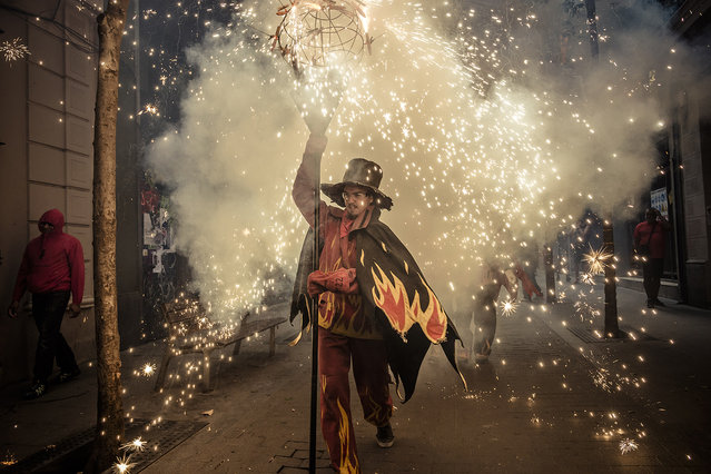 """Children in devil costumes dance to traditional drums, beneath exploding fireworks during the """"correfocs"""" fire-runs at the end of the Festa Major de Gracia in Vila de Gracia, Catalonia, Spain on August 21, 2016. (Photo by Matthias Oesterle/ZUMA Press/Splash News)"""