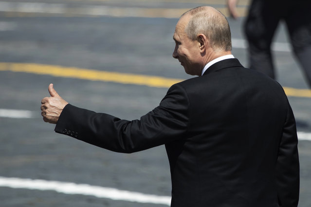 Russian President Vladimir Putin gestures as he leaves Red Square after the Victory Day military parade marking the 75th anniversary of the Nazi defeat in Moscow, Russia, Wednesday, June 24, 2020. Russian President Vladimir Putin hailed the defeat of Nazi Germany at the traditional massive Red Square military parade, which was delayed by more than a month because of the invisible enemy of the coronavirus. The parade is usually held May 9 on Victory Day, Russia's most important secular holiday but was postponed until Wednesday due to the pandemic. (Photo by AP Photo/Pavel Golovkin, Pool)