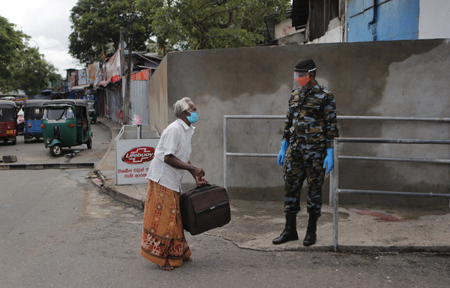 A stranded Sri Lankan inquires about transportation from a government soldier in Colombo, Sri Lanka, Monday, May 11, 2020. Sri Lanka's government asked state and private sector workers to resume work Monday after a nearly two-month coronavirus lockdown. (Photo by Eranga Jayawardena/AP Photo)