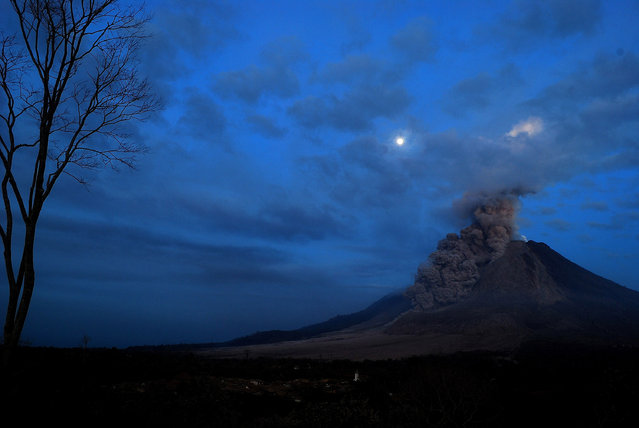 This long exposure photograph taken early on October 10, 2014 shows giant ash clouds released from the crater during the eruption of Mount Sinabung volcano as seen from Karo district located in Sumatra island. (Photo by Sutanta Aditya/AFP Photo)