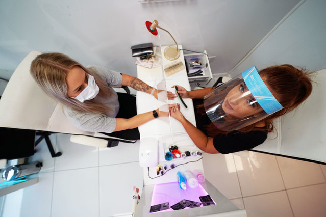 Beautician Alex Smith, 26, does the nails of Jules Aspen, 40, at the Madame Beauty salon in Chirton, North Tyneside, UK on July 13, 2020. Nail bars, beauty salons, tattoo and massage studios, physical therapy businesses, spas and piercing services are able to reopen in the latest lifting of restrictions in England. (Photo by Owen Humphreys/PA Images via Getty Images)