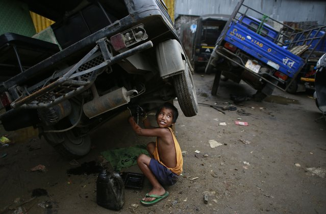 Biswa Gurung, a seven-year-old Indian boy talks to a colleague as he works at an automobile workshop in Gauhati, India, Sunday, October 12, 2014. Despite the country's rapid economic growth, child labor remains widespread in India, where an estimated 13 million children work, with laws meant to keep kids in school and out of the workplace routinely flouted. (Photo by Anupam Nath/AP Photo)