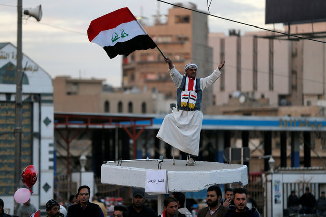 An Iraqi man holds an Iraqi flag as he celebrates the final victory over the Islamic State at Tahrir Square in Baghdad, Iraq December 10, 2017. (Photo by Thaier Al-Sudani/Reuters)