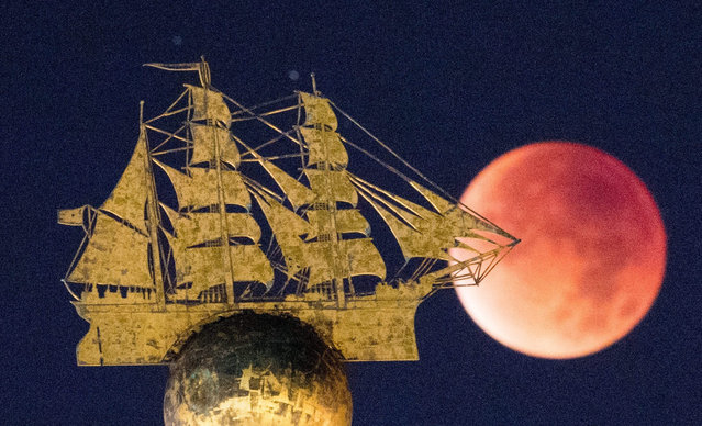 The perigee full moon, or supermoon, appears red behind the sculpture of a sailing ship in Hamburg, Germany, 28 September 2015. The combination of a supermoon and total lunar eclipse last occurred in 1982 and will not happen again until 2033. (Photo by Daniel Reinhardt/EPA)