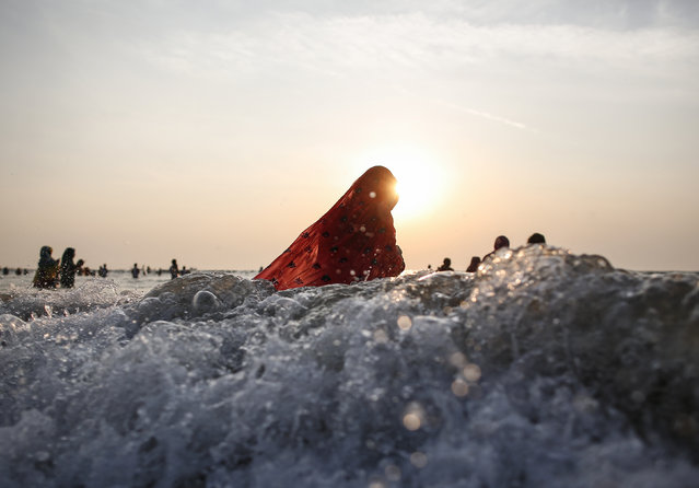 A Hindu devotee prays while standing in the waters of the Arabian Sea as she worships the Sun god Surya during the Hindu religious festival Chatt Puja in Mumbai October 29, 2014. (Photo by Danish Siddiqui/Reuters)