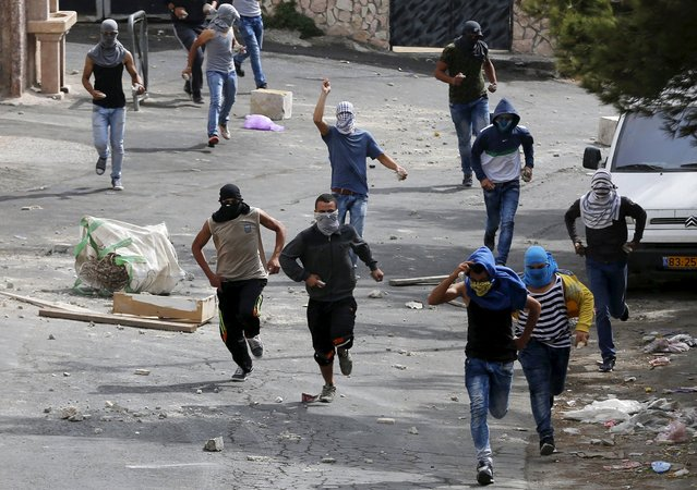 Masked Palestinians throw stones during clashes with Israeli police in Sur Baher, a village in the suburbs of Arab east Jerusalem, October 7, 2015. (Photo by Ammar Awad/Reuters)