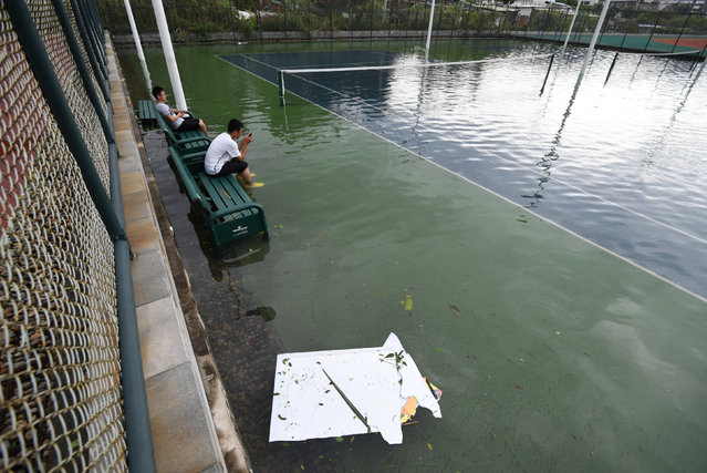 People sit on bench inside a flooded tennis court after Typhoon Meranti makes a landfall on southeastern China, in Xiamen, Fujian province, China, September 15, 2016. (Photo by Reuters/Stringer)