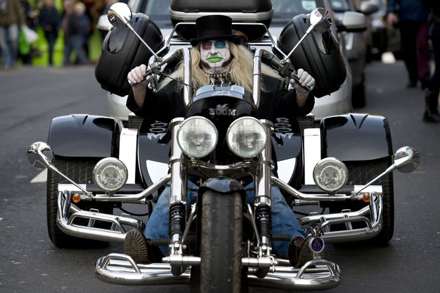 "A man wearing a costume drives a motorcycle through Whitby  during the biannual ""Whitby Goth Weekend"" (WGW) festival in Whitby, Northern England, on November 2, 2014. (Photo by Oli Scarff/AFP Photo)"