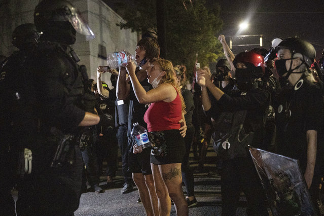 Protesters standoff with police as they take to the streets Friday, September 4, 2020 in Portland, Ore.  This weekend Portland will mark 100 consecutive days of protests over the May 25 police killing of George Floyd. (Photo by Paula Bronstein/AP Photo)