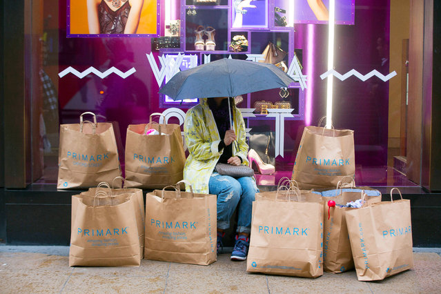 A lone shopper holds an umbrella as she sits surrounded by 12 Primark-branded paper shopping bags outside a Primark clothing store, operated by Associated British Foods Plc, on Oxford Street in London, U.K., on Monday, November 3, 2014. (Photo by Jason Alden/Bloomberg)