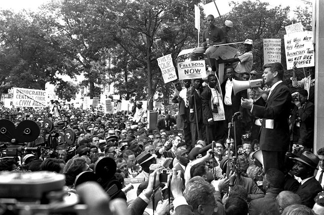 Attorney General Robert Kennedy uses a bullhorn to address black demonstrators at the Justice Department, on June 14, 1963. The demonstrators marched to the White House, then to the District Building, and wound up at the Justice Department. (Photo by AP Photo/STF)