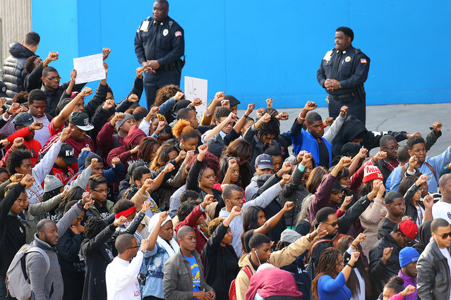 A law enforcement officers watch as Morehouse College students, who marched from campus, raise their fists in the air joining others in a rally and protest at the CNN Center, Tuesday, November 25, 2014, in Atlanta, the day after a grand jury's decision not to indict a white Ferguson, Mo., police officer who killed Michael Brown, an unarmed black teen. (Photo by Curtis Compton/AP Photo/Atlanta Journal-Constitution)