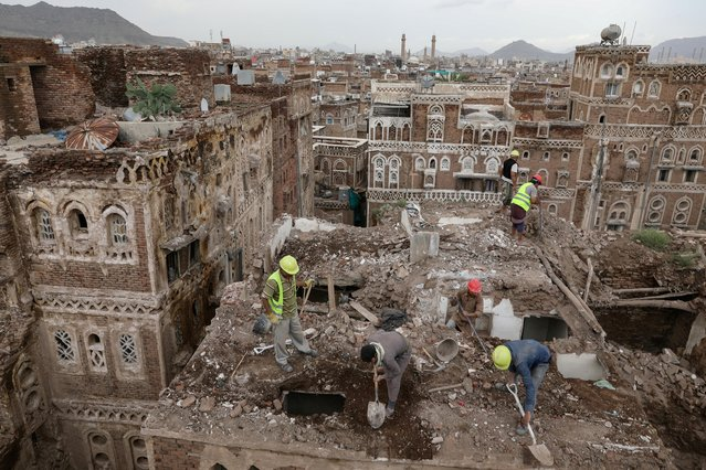Workers demolish a building damaged by rain in the UNESCO World Heritage site of the old city of Sanaa, Yemen on August 9, 2020. (Photo by Khaled Abdullah/Reuters)