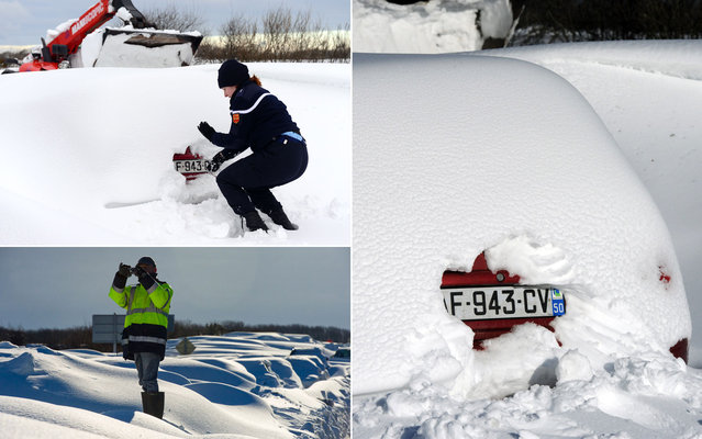 Police digs the snow to identify the license plate of a car after a snowstorm in road near Beaumont-Hague, in northwestern France, on March 13, 2013. More than 68,000 homes were without power in the region, which came on orange alert. (Photo by Alain Jocard/AFP Photo)
