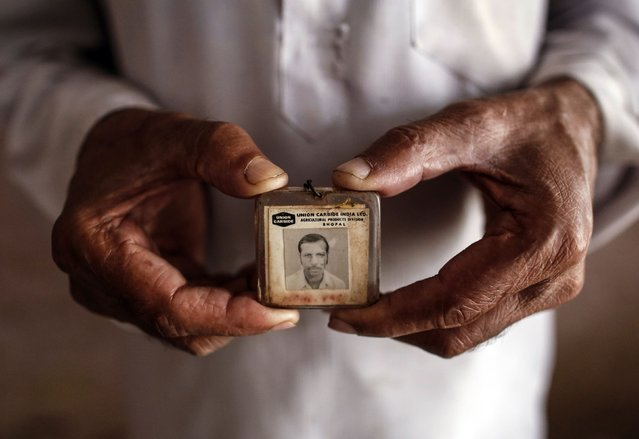 Former maintenance worker, Mohammed Yaqub, poses in his house with his old identity card from the defunct Union Carbide pesticide plant in Bhopal where he once worked November 13, 2014. (Photo by Danish Siddiqui/Reuters)