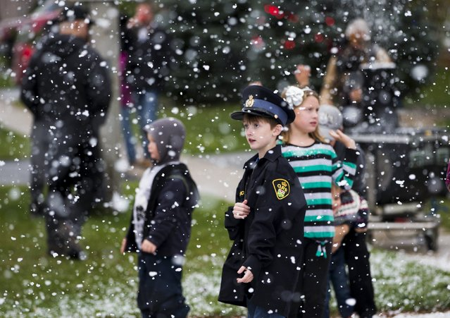 Logan Leversage, brother of terminally-ill boy Evan Leversage, looks on in fake snowfall in St. George, Ontario, Canada October 24, 2015. (Photo by Mark Blinch/Reuters)