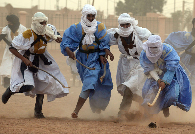 Nomads vie for the ball during a match of nomad hokey, played on sand, in the Moroccan desert in M'hamid El Ghizlane, southeast of Zagora, on March 20, 2013. (Photo by Fadel Senna)